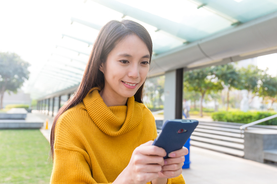 Asian Young Woman play the game though mobile phone